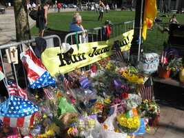 "Photograph of a large banner reading ""Run Jane Run,"" surrounded by flowers and balloons, Copley Square memorial. The inscription on the top left of the banner reads: ""In 1996 my wife Jane was one of 40,000 runners at the 100th Boston Marathon. It would be easier to spot the family, so I made 2 banners. They have stayed in my studio for 18 years. Now they have a purpose. I believe one day Jane Richard who lost her brother and her leg will one day run the Boston Marathon in his honor and in memory of all those affected by a senseless act. I hope Jane and all those affected will see this banner and when you run Boston you will see the second banner just like it and know that those who signed it will never forget the events of 4-15-2013 and we will always support you. -K. McGovern(?)"""