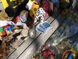 Photograph of a bench with small stuffed animals, flowers, and packets of seeds for forget-me-not flowers at the Copley Square memorial.