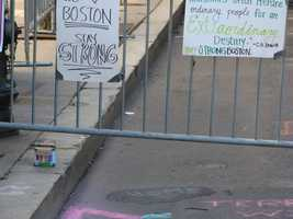 A box of chalk sits next to messages written on Boylston Street and signs posted on a makeshift memorial at Copley Square. This photo was taken on Wednesday, April 17th, 2013 (two days after the marathon bombings).
