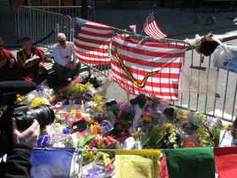 "Image of flowers, flags, and mourners at a makeshift memorial for the 2013 Boston Marathon. Photo taken on Wednesday, April 17th (two days after the bombings). Items photographed include an American flag that reads ""Don't Tread on Me"" and a handmade sign that says ""BOSTON will OVERCOME."""