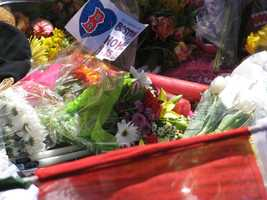 "Flowers left at a makeshift memorial in Copley Square on Wednesday, April 17th 2013 (two days after the marathon bombings). A sign on one bouquet of flowers clearly reads ""No Matter WHAT Boston You're My HOME."""