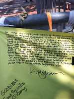 """This is one of a series of photos I took on the last day of the Copley Square memorial site for the Boston Marathon bombings.My transcription of this hand-written sign is as follows:""""In 1996 my wife Jane was 1 of 40,000 runners in the 100th Boston Marathon. It would be easier for her to spot the family so I made 2 banners. They have stayed in my studio for 18 years. Now they have a purpose. I believe one day Jane Richards who lost her brother and her leg will one day run the Boston Marathon in his honor and memory of all those affected by a senseless act. I hope Jane and all those affected will [...] this banner and when you run Boston you will see the second banner just like it and know that those who signed it will never forget the events of 4-15-2013 and we will always support you.K. McGovernGod BlessGood PrevailsP Geary""""The memorial featured a collection of well-wishes and messages of sympathy, hope, and strength. It was taken down on June 25, 2013, and its contents will be archived in a more permanent location."""