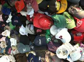 These hats are part of a larger collection of materials left on the ground in a makeshift memorial in the public park by the Copley MBTA station.