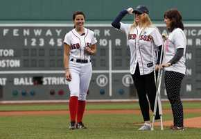 Boston Marathon bombing victim Heather Abbott, center, of Newport, R.I., throws out the ceremonial first pitch before a baseball game between the Boston Red Sox and the Toronto Blue Jays in Boston, May 11, 2013.