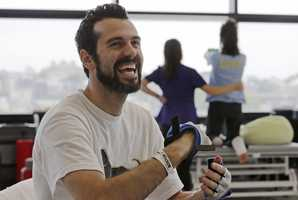 """In this May 22, 2013 photo, Boston Marathon bombing survivor Pete DiMartino, of Rochester, N.Y., smiles during a physical therapy session at the Spaulding Rehabilitation Hospital in Boston. DiMartino was injured in an explosion near the finish line, which blew away much of one leg and burned the other. """"I don't want anybody feeling sorry for me,"""" he said. """"... I want people to see that this has made me a better person and I want people to become better people through what they see through me."""""""