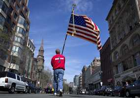 Lt. Mike Murphy of the Newton, Mass., fire dept., carries an American flag down the middle of Boylston Street after observing a moment of silence in honor of the victims of the bombing at the Boston Marathon near the race finish line, Monday, April 22, 2013, in Boston, Mass. At 2:50 p.m., exactly one week after the bombings, many bowed their heads and cried at the makeshift memorial on Boylston Street, three blocks from the site of the explosions, where bouquets of flowers, handwritten messages, and used running shoes were piled on the sidewalk.
