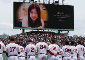 The Boston Red Sox stand during the tribute to Boston Marathon bombing victims, including Chinese student Lingzi Lu, before a baseball game against the Kansas City Royals in Boston, April 20, 2013.