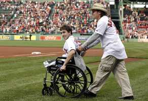 Boston Marathon bombing survivor Jeff Bauman, left, is wheeled out by Carlos Arredondo, the man who helped save his life, to throw out the ceremonial first pitch at Fenway Park prior to a baseball between the Boston Red Sox and the Philadelphia Phillies, May 28, 2013, in Boston.