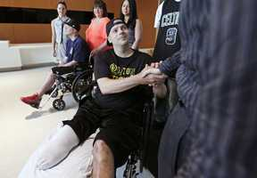 Boston Marathon bombing survivor J.P. Norden, of Stoneham, Mass., shakes hands with his physician Dr. David Crandell while getting released from Spaulding Rehabilitation Hospital in Boston, May 31, 2013. At far left is J.P.'s brother Paul Norden, who was released earlier in the month.