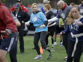 Heather Abbott, center, who lost part of her left leg in the 2013 Boston Marathon explosion, is assisted by physical therapist Dan Connors, top right, as she performs an agility drill during a running clinic for challenged athletes, Oct. 6, 2013, in Cambridge, Mass. Abbott was fitted with a running prosthetic on Saturday and was trying it out in the rain a day later.