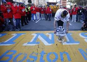 Boston Red Sox's Jonny Gomes places the championship trophy and a Red Sox baseball jersey at the Boston Marathon Finish Line during a pause in their World Series victory rolling rally in Boston, Nov. 2, 2013, to remember those affected by the Marathon bombing.