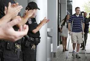 Transit police officer Richard Donohue, front right, leaves Spaulding Rehabilitation Hospital in Boston, followed by his wife Kim, center, June 14, 2013. Dononhue was injured during a shoot-out with the Boston Marathon bombing suspects.