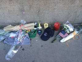 A memorial grows outside the fire house.