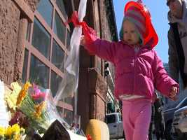 A child leaves flowers at the Boylston Street fire house Thursday morning.