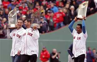 Former Red Sox players, from left, Mike Lowell, Jason Varitek and Pedro Martinez hold World Series trophies