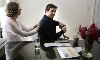In this March 14, 2014 photo, Jeff Bauman, who lost both his legs above the knee in the Boston Marathon bombing, smiles as his fiancee Erin Hurley touches his back while seated at the kitchen counter of their Carlisle, Mass., home. The couple are expecting their first child in July.
