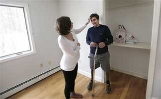 In this March 14, 2014 photo, Jeff Bauman smiles as his fiancee Erin Hurley touches his hair in the soon-to-be nursery of their Carlisle, Mass., home. The couple are expecting their first child in July.