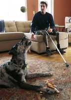 In this March 14, 2014 photo, Jeff Bauman, plays catch with his dog Bandit, at his Carlisle, Mass., home.