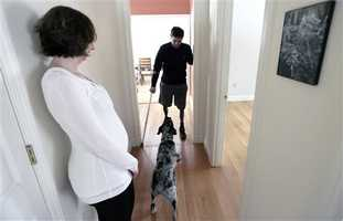 In this March 14, 2014 photo, Jeff Bauman, talks to his dog Bandit as his fiancee Erin Hurley watches at their Carlisle, Mass., home. Bauman, who lost both his legs above the knee in the Boston Marathon bombing, is learning to adjust to his prosthetics. It takes more energy to walk with prosthetics, which means he gets tired more easily.