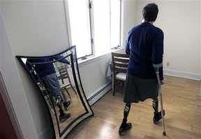 In this March 14, 2014 photo, Jeff Bauman walks past a mirror at his home in Carlisle, Mass. Bauman, who lost both his legs above the knee in the Boston Marathon bombing, played a key role in identifying the men suspected of placing the two devices.