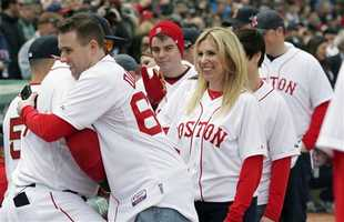 MBTA police officer Richard Donohue, left, hugs Boston Red Sox's David Ortiz as Boston Marathon bombings survivor Heather Abbott, center, stands nearby before the Red Sox's baseball homer-opener against the Milwaukee Brewers at Fenway Park in Boston, Friday, April 4, 2014.