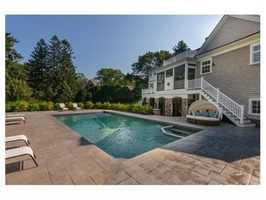 Grounds include a spacious yard and custom designed gunite pool with lovely blue stone patio.