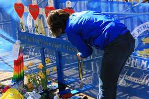 A woman wearing a 2013 Boston Marathon jacket drops off a medal at the memorial at the finish line.