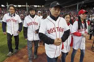 """Family members of Boston Marathon bombing victim Lu Lingzi walk off the field after announcing """"play ball"""" during ceremonies marking the one-year anniversary of the bombings before a baseball game between the Boston Red Sox and the Baltimore Orioles in Boston, Sunday, April 20, 2014."""