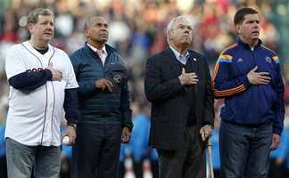 Founder of The One Fund Jim Gallagher, left, Massachusetts Gov. Deval Patrick, center left, former Boston mayor Tom Menino, center right, and current mayor Marty Walsh, right, stand on the field at Fenway Park for the playing of the national anthem during ceremonies marking the one-year anniversary of the Boston Marathon bombings before a baseball game between the Boston Red Sox and the Baltimore Orioles in Boston, Sunday, April 20, 2014.