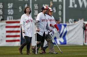 Boston Marathon bombing survivors including Jeff Bauman, center left, and Carlos Arredondo, center right, walk onto the field at Fenway Park during ceremonies marking the one-year anniversary of the bombing before a baseball game between the Boston Red Sox and the Baltimore Orioles in Boston, Sunday, April 20, 2014.