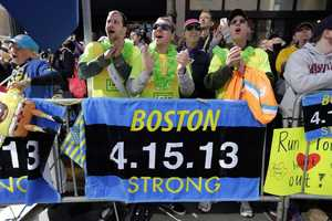 Race fans from left, Andrew Lembecke, of Chicago, Brandon Petrich of Fargo, N.D, Marlene Youngblood of Louisville, Ky, and Bill Januszewski cheer near the finish line at the 118th Boston Marathon Monday, April 21, 2014 in Boston.