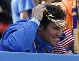 Boston Marathon bombing hero Carlos Arredondo tries on a victor's wreath near the finish line of the 118th Boston Marathon.