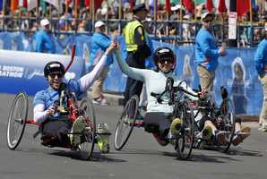 Boston Marathon husband and wife bombing survivors Patrick Downes and Jessica Kensky, who each lost a leg in last year's bombings, roll across the finish line in the 118th Boston Marathon Monday, April 21, 2014 in Boston.