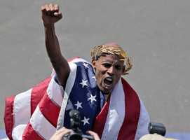 With an American flag wrapped around him, Meb Keflezighicelebrates his victory in the 118th Boston Marathon Monday, April 21, 2014 in Boston.