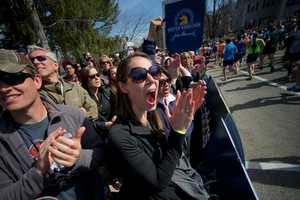 Shayna Clancy (center) of Durham, NC, cheers the runners on at the starting line of the Boston Marathon in Hopkinton, Mass.