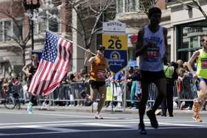 Donny Sazama, of Hermantown, Minn., carries an American flag as he runs past the 26 mile mark of the 118th Boston Marathon Monday, April 21, 2014 in Boston.
