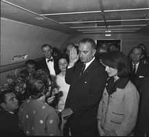 "Thomas ""Lem"" Johns was a Secret Service agent at the side of President Lyndon Johnson in the chaotic aftermath of the assassination of John F. Kennedy. Johns is pictured in iconic photos from Nov. 22, 1963 aboard the presidential plane where Johnson was sworn in during a hastily-arranged ceremony. This photo shows Johns center right, partially obscured by former First Lady Jacqueline Kennedy as Johnson takes the oath of office.  (December 11, 1925 – May 10, 2014)"