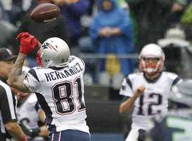New England Patriots quarterback Tom Brady (12) looks on as Aaron Hernandez (81) fails to catch a pass after in an NFL football game against the Seattle Seahawks, Sunday, Oct. 14, 2012, in Seattle. The Seahawks won 24-23.