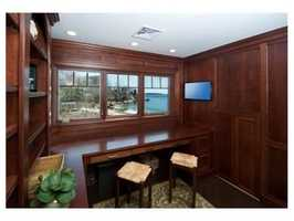 The second level includes a wood paneled office, three en suite additional bedrooms, and a reading nook.