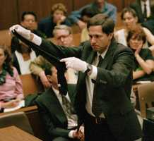 California Department of Justice criminalist Gary Sims shows the jury one of Simpson's blood-stained socks Wednesday, May 31, 1995. DNA analysis of blood found on the socks found in Simpson's bedroom identified it as Nicole Brown's.  Defense medical expert Dr. Henry Lee testified the police collection procedure of the socks could have caused contamination.