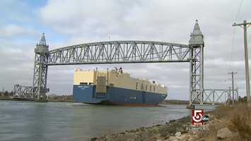 A massive, 652 foot, 672 ton, car carrier, passes under the railroad bridge.