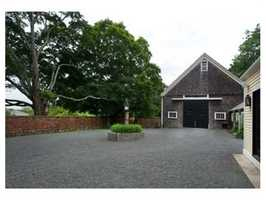 Lovely walled courtyard for parking leads to an 8-stall horse barn with adjacent tack room.