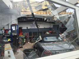 A Jaguar convertible sits inside a heavily-damaged auto shop in Revere.