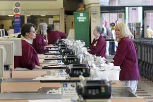 Cashiers and baggers sit idle at the Market Basket supermarket chain Thursday July 24, 2014, in Concord, N.H.
