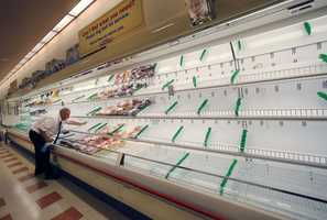 Meat manager Dave Fillebrown wipes down largely empty shelves Thursday, July 24, 2014 at a Market Basket supermarket in Haverhill, Mass.