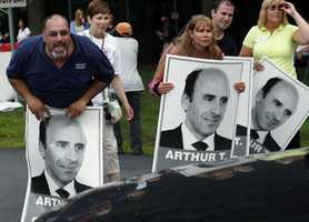 """Protesters holding """"Arthur T"""" signs taunt an occupant of a car driving from a Market Basket Supermarket job fair in Andover, Mass., Monday, Aug. 4, 2014."""