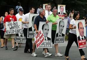 """Protesters holding """"Arthur T"""" signs picket outside a Market Basket Supermarket job fair in Andover, Mass., Monday, Aug. 4, 2014."""