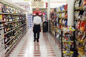 A customer walks by the empty produce isle Thursday July 24, 2014 at a Market Basket supermarket in Concord, N.H.