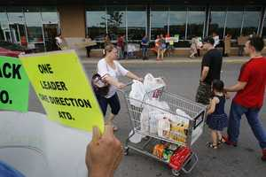 Demonstrators, left and behind, display placards outside a Market Basket grocery store as a shopper pushes a grocery cart, center, Tuesday, July 22, 2014, in Chelsea, Mass.