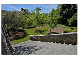 The grounds are surrounded by granite block walls, mature plantings, and peaceful conservation land.